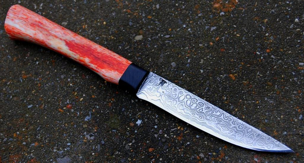 Puukko lame de 11 cm forgée en damas , garde et en ébène , manche en os stabilisé teinté disponible